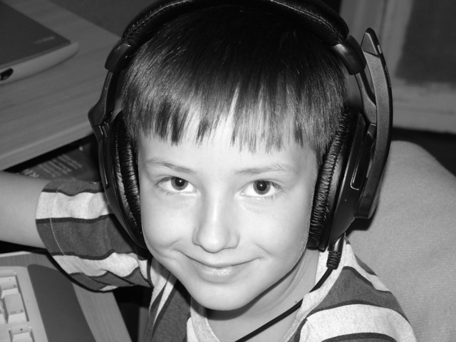 malý kluk poslouchající hudbu skrze velká sluchátka